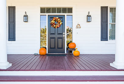 White house with black door and pumpkins on porch