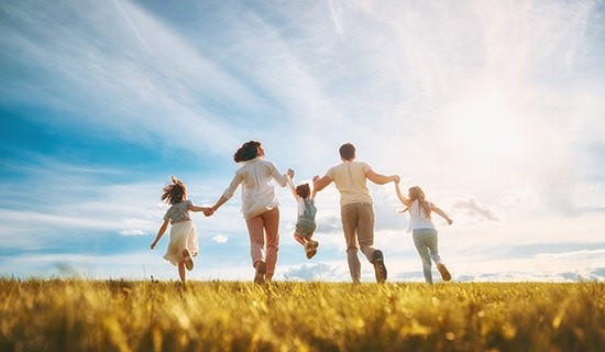 young family running through a field with blue sky